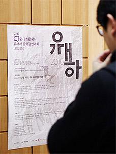 유재하음악경연대회 포스터를 바라보고 있는 사람의 모습입니다.