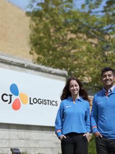 CJ Logistics''로 브랜드가 통합된 CJ대한통운 미 통합법인의 현판 앞에서 파란색 유니폼을 입은 직원들이 기념촬영을 하고 있다.